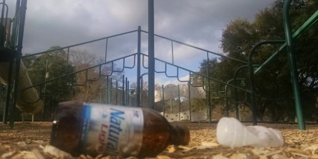 An empty beer bottle and other trash sits in the main play area of Eastside Park Monday, Feb. 23