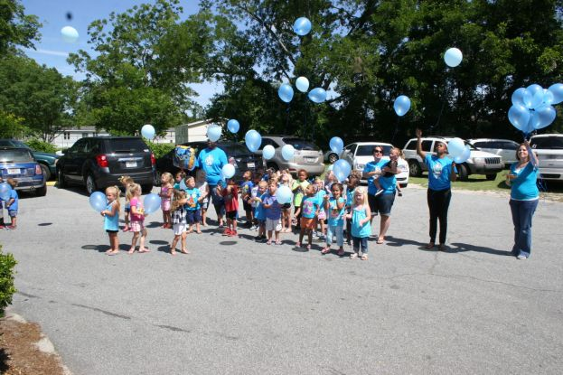 Staff and students at Precious Possessions release blue balloons in memory of the late Eli Johnson, 2, who drowned Sunday, June 22, in Douglas.