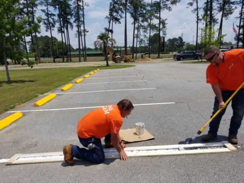 Pictured: ESG, Operations Leadership volunteers painting and working on the stripping for the parking lot