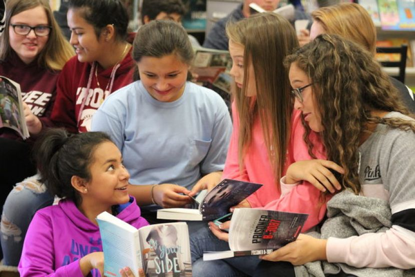 Daniella Sanchez, Jaedon Arvidson, Madison Strickland, and Reagan Thomas discuss a book they got at the book fair