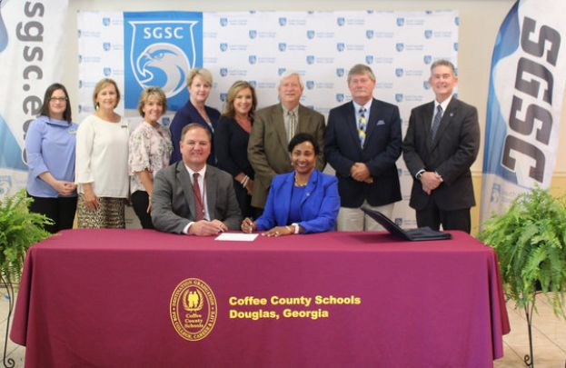 L - R: In attendance for the signing in Douglas were Dr. Jodi Fissel, SGSC Dean of the School of Arts and Professional Studies; Kim Clayton, Director of Personnel; Dr. Christina Tucker, Director of Federal Programs; Dr. Joy Perren, Director of Assessment and Accountability; Kim Miller, Assistant Superintendent of Curriculum and Instruction; Dr. Carl McDonald, SGSC Academic Affairs Specialist; Dr. Kit Carson, SGSC Department Chair for Teacher Education; Dr. Robert Page, SGSC Vice President for Academic and Student Affairs and seated is Dr. Morris Leis, Superintendent with Dr. Ingrid Thompson-Sellers, SGSC President.