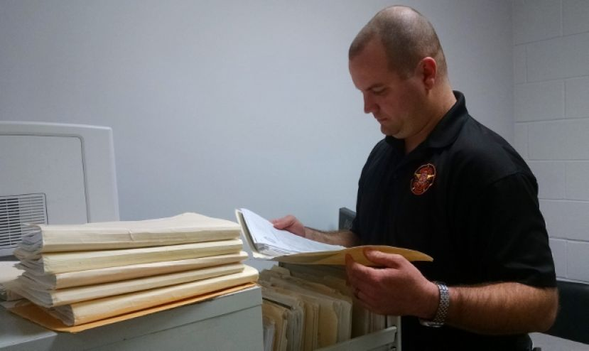 Coffee County Sheriff's Detective Jason Whiddon combs through his files on local sex offenders Wednesday at the law enforcement center.