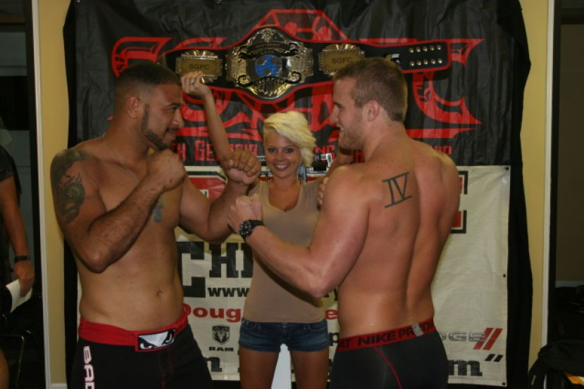 Amy Verlinda holds the SGFC light heavyweight belt as Sammy 'Lights Out' Elisis (left) and Willy 'Right Hook' Wright (right) square off at the Border Wars weigh-in Friday afternoon at Coffee Chrysler in Douglas.