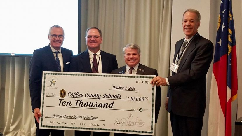 Dr. Morris Leis, school superintendent, accepts a check for $10,000 from the Georgia Association of Realtors after the Coffee County School System was named the 2018 Charter System of the Year.