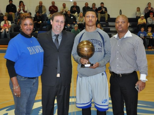Jovante' Spivey (second from right) was recognized February 11 for being the first player to eclipse 1,000 points in a career at SGSC. (L-R) Nicole Spivey (mother), SGSC head coach Cory Baldwin, Spivey, and Anthony Spivey (father).