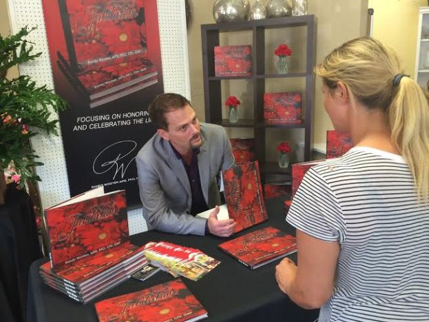 Randy Wooten signs a copy of Jubilation at Delorice's Florist on Thursday, July 9, 2015.