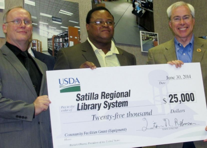 From left, Satilla Regional Library Director Mark Cole, State Director for USDA Rural Development Quinton Robinson, and Congressman John Barrow commemorate the receipt of a $25,000 grant from the USDA to the library system Monday, June 30, at the Douglas-Coffee County Public Library.