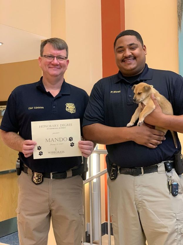 Police chief Shane Edmisten (left) and police officer Patrick West (right) show off the department's newest officer, Mando, and the honorary criminal justice degree that Wiregrass Technical College presented to Mando this morning at the Douglas campus.