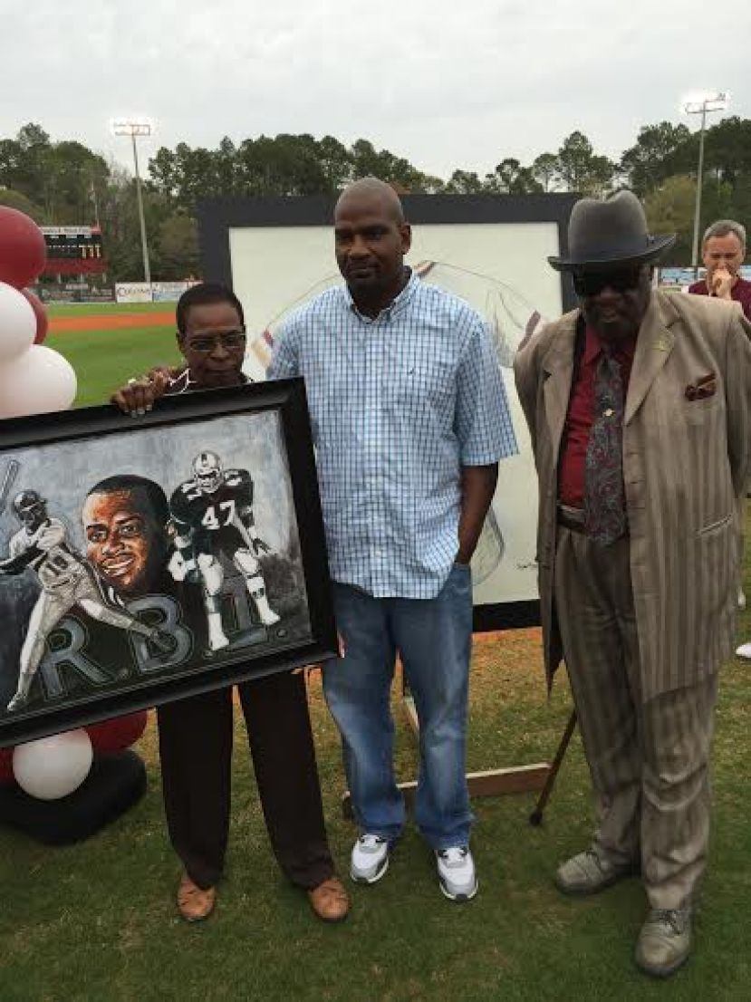 Robbie Ingram, Reggie Ingram, and Johnnie Lee Roper display the second piece of Dylan Ross artwork that the Coffee baseball team presented to the family of Riccardo Ingram before Friday night's baseball game against Brunswick.