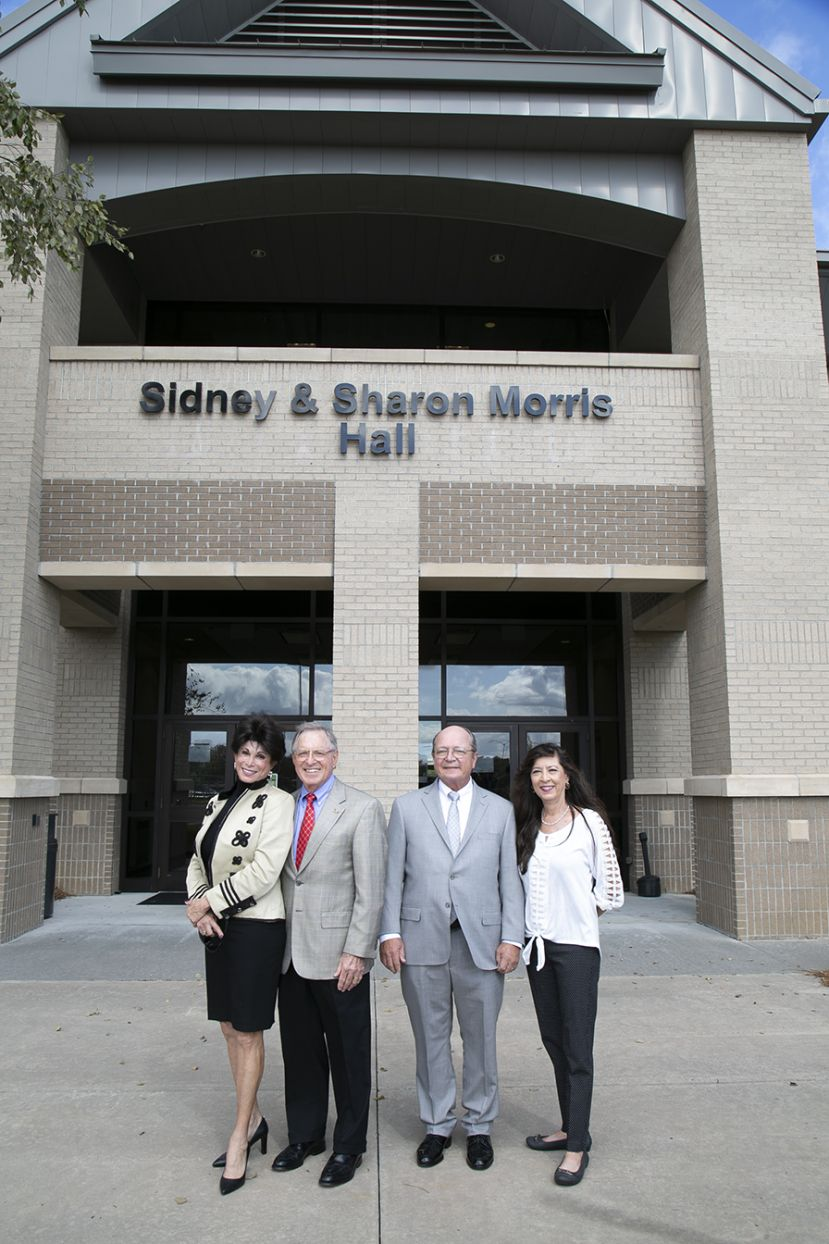Wiregrass supporters Sharon and Sidney Morris and Dr. Edward and Rhonda Mark stand in front of the newly named Sidney and Sharon Morris Hall.  The new Health Sciences Building is currently under construction to the left of this building and when it opens in Spring 2022 will be named Edward and Rhonda Mark Health Sciences Building.