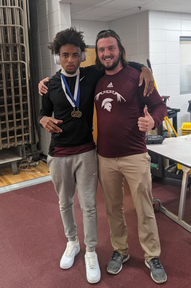 Region 1-5A triple jump champion Chris Stafford (left) and one of Coffee High's coaches, Zack Marx (right)